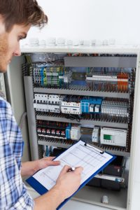 Cropped image of male technician holding clipboard while examining fusebox